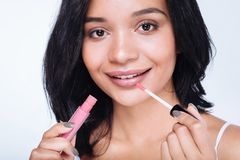 Close up of a pretty woman applying lip gloss. Charming beauty. The close up of a pretty young woman with a swarthy complexion applying pink lip gloss to her Stock Photo