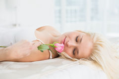 Close up of a pretty woman in bed with a rose Royalty Free Stock Photos