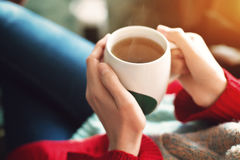 Close up of pretty woman`s hands in red sweater holding cup of tea in the morning sunlight.