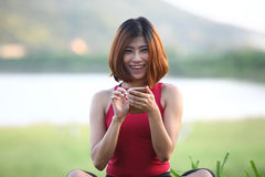 Close up pretty woman sit on lawn play her smartphone and smile Royalty Free Stock Images