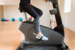 Close up of pretty woman workout on cycling in fitness gym., Spo. Rts and healthy concept Stock Photo