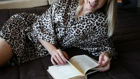 Pretty young woman enjoying reading a book at home lying on bed smiling in pleasure in dressing gown. Close up of pretty young blonde woman enjoying reading a stock footage
