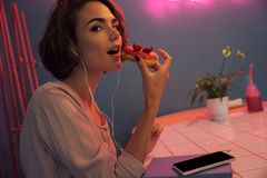 Close up of a pretty young girl in earphones. Eating a donut while sitting in a cafe and looking at camera Stock Photography