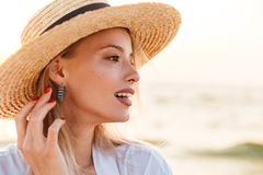 Close up of a pretty young girl in summer hat. At the beach looking away Stock Images