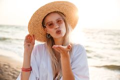 Close up of a pretty young girl in summer hat. And sunglasses at the beach sending a kiss Stock Photos