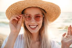 Close up of a pretty young girl in summer hat. And sunglasses at the beach looking at camera Stock Image