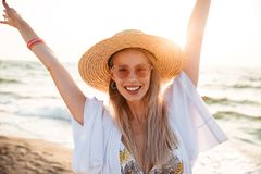 Close up of a pretty young girl in summer hat and sunglasses. At the beach looking at camera, having fun Stock Photography