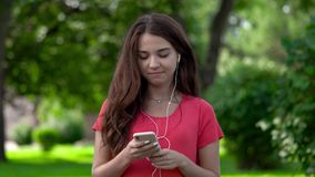 A close-up of a pretty young woman wearing earphones and listening to music, she is moving to the tune. She is relaxing. In the nature stock footage
