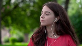 A close-up of a pretty young woman wearing earphones and moving in tune. She is outside in the nature stock footage