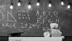 Close up of primary school classroom. Classroom with chalkboard on background. Childish desk with alarm clock and teddy. Bear. Primary school concept. Classroom stock image