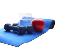 Close up of a pristine red apple two dumbbells  and glass water, blue atheletic small. Rug of  isolated on white with reflection , sound lifestyle Stock Photo