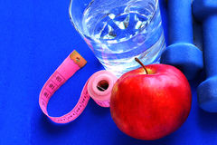 Close up of a pristine red apple two dumbbells  and glass water. Blue atheletic small rug of   with reflection , sound lifestyle Stock Photo