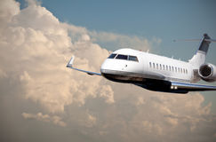 Close up of a private jet flying through cloudy skies Stock Photos