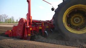 Close-up, proces van gemechaniseerde machine die potatoe planten de grote tractor met speciaal materiaal maakt Lange rijen met pl stock videobeelden