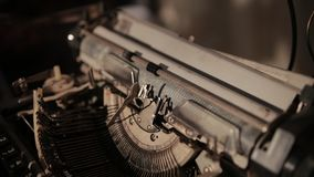 Close-up of process of ancient printing machine, slow motion. Close-up of process of ancient printing machine, man in white gloves presses keyboard, slow motion stock video