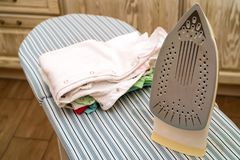 Pressboard and iron. Close-up of process ironing clothes on press board Stock Photo