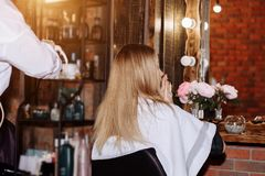 Close up of process straightening long blonde hair with hair irons. Beauty, hairstyle, hot styling, keratin straightening concept stock photos
