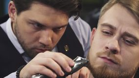 Close up of a professional barber trimming beard of a young man. Sliding close up shot of a handsome young man getting his beard trimmed by a professional barber stock footage