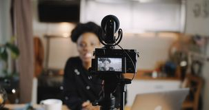 Close-up professional camera is filming young beautiful African blogger woman creating new vlog video slow motion. Successful black female vlogger working at stock footage