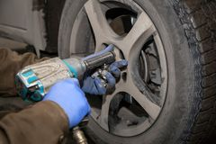 Repair service station. Close up Professional car mechanic changing car wheel in auto repair service. Autoworker doing tire or wheel replacement in garage of stock images