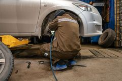 Repair service station. Close up Professional car mechanic changing car wheel in auto repair service. Autoworker doing tire or wheel replacement in garage of stock photography