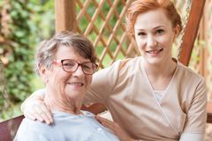 Close-up of a professional caregiver sitting next to and holding royalty free stock image