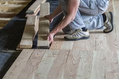 Close up of professional carpenter installing natural wooden new planks on cement floor in empty unfinished room under reconstruct