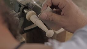 Close-up of a professional carpenter using sandpaper to grind a piece of wood on a lathe