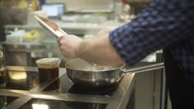 Close-up of professional chef frying in pan in kitchen. Action. Appetizing cooking chef with fried products on fuming. Pan in kitchen of restaurant stock video footage