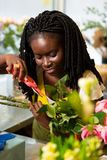 Close up of professional gardener that cutting leaves. Plant care. Amazing dark-skinned decorator expressing positivity while composing bouquet stock photo