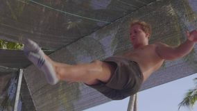 Professional gymnast jumping on the trampoline and doing tricks in slow motion. Close-up of professional gymnast with bare core jumping on the trampoline and stock video footage