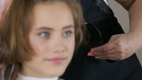Close up professional hairdresser, stylist coloring teen girl hair. In white make up room stock video