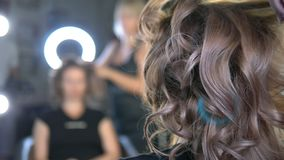 Close-up. Professional hairdresser using curling iron. Hair curls in salon,. Professional hairdresser using curling iron. Hair curls in salon stock footage