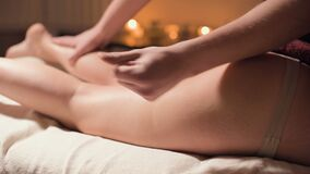 Close-up professional hip massage in the spa salon with a pleasant warm light. A male masseur does a premium massage to