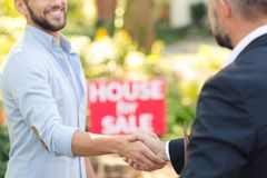 House seller shaking buyer`s hand. Close-up of professional house seller in suit shaking hand of buyer of a new home stock photography