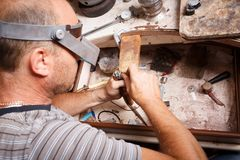 Close-up jeweler working. Craftsman making jewelry on a workshop background. Accessory making concept. stock photo