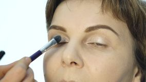 Close-up of professional make-up artist applying eyeliner on eyelid. fashion industry cosmetics. Finishing contour detail stock footage