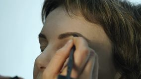 Close-up of professional make-up artist applying eyeliner on eyelid. Stylist is doing make up for female by eyeliner stock video footage