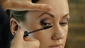 Close-up of professional make-up artist dyes the eyes of the model with a large brush. fashion industry cosmetics.  stock video