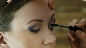 Close-up of professional make-up artist dyes the eyes of the model with a large brush. fashion industry cosmetics.  stock video footage