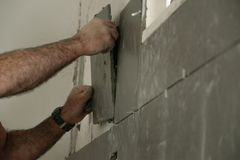 Close Up of professional mason worker indoor - laying tiles stock photography