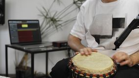 Close up of musician playing djembe drum instrument in home music studio. Close up of professional musician recording djembe drum instrument in digital studio stock video footage