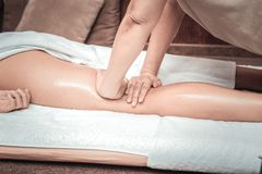 Close up of professional skilled masseuses hands. Best body massage. Close up of professional skilled masseuses hands while doing the body massage stock images