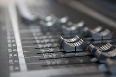 Close up professional studio mixing console fader in grey. A industry studio mixing console. Close up makro photo of volume faders in grey with soft bokeh Royalty Free Stock Image