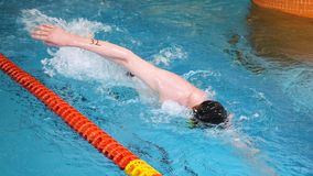 Close up for professional swimmer in slow mothion while swimming race in indoor pool. Athlete training, swimming the