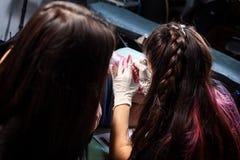 Tattooist woman making tattoo. Close up of professional tattoo artist makes a tattoo red bird on the femur in dark tattoo studio, back view stock image