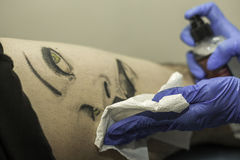 Close up professional woman tattooer cleaning tattoo in a man le Stock Image