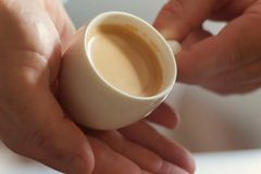 Close up profile of a man hands relaxing holding a cup of coffee. In a wooden table at home with a window in the background Stock Image