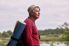 Close up profile shot of eldery man with backpack, wearing red casual sweater and cap, standing near river and looking far away,. Senior male likes to spend royalty free stock photo