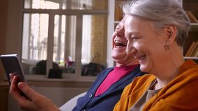 Close-up profile shot of senior caucasian spouses talk in online videochat with their friends on tablet at cozy home. stock footage